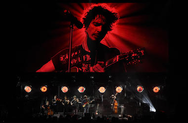 """Singer Ryan Adams performs with his band underneath an image of the late singer Chris Cornell during """"I Am The Highway: A Tribute to Chris Cornell"""" at The Forum, Wednesday, Jan. 16, 2019, in Inglewood, Calif. (Photo by Chris Pizzello/Invision/AP)"""