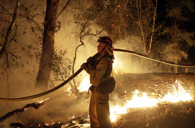 In this Oct. 14, 2017 file photo, a firefighter holds a water hose while fighting a wildfire in Santa Rosa, Calif. Investigators say the deadly 2017 wildfire that killed 22 people in California's wine country was caused by a private electrical system, not