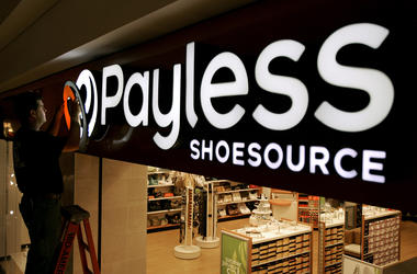 In this May 18, 2006, file photo a worker puts the finishing touches on a sign unveiling the company's new look at a Payless Shoesource store at a mall in Independence, Mo. Payless ShoeSource has filed for Chapter 11 bankruptcy protection and is shutterin