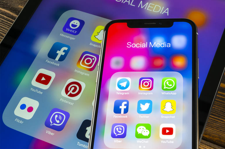 Apple iPad and iPhone X with icons of social media facebook, instagram, twitter, snapchat application on screen. Social media icon.