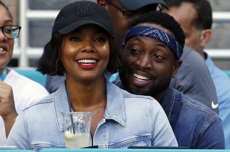 In this Sunday, Oct. 14, 2018 file photo, Miami Heat player Dwyane Wade and his wife Gabrielle Union-Wade acknowledge the cheers from the crowd during the second half of an NFL football game between the Miami Dolphins and the Chicago Bears in Miami Garden