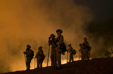 Firefighters hold a line in the Camp Fire with a control burn near Bloomer Hill in Butte County in California.