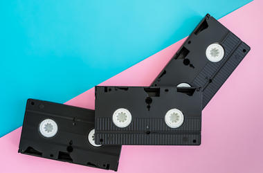 3 black VHS video tapes lying diagonally on a bright pink and blue background.