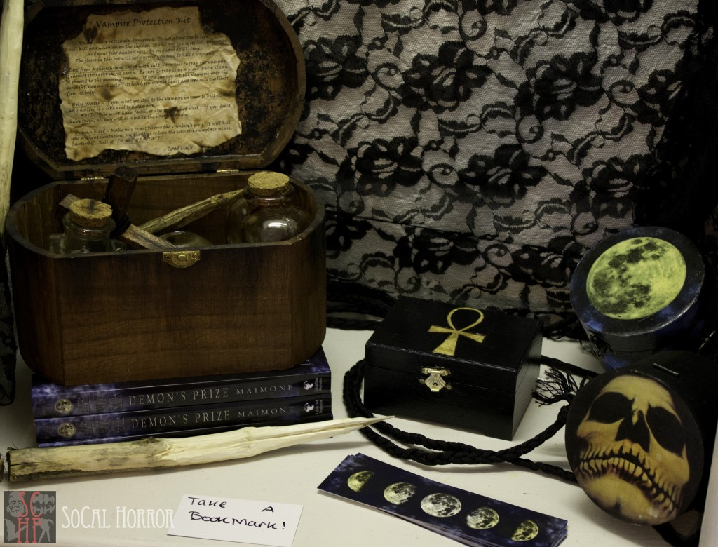 A vampire defense kit sits atop a few copies of Demon's Prize, all created by author, Jennifer Maimone