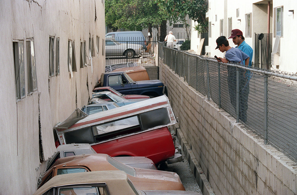 Two men inspect damage to cars and a soft-story apartment building in Canoga Park after the Northridge earthquake on January 21, 1994.