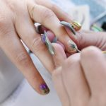 Christina Blea paints a pot leaf design onto the nails of writer Emily Earlenbaugh, in Christina's Dabulous Nail Bar, at her home in Richmond, Calif., on Wednesday January 31, 2018.