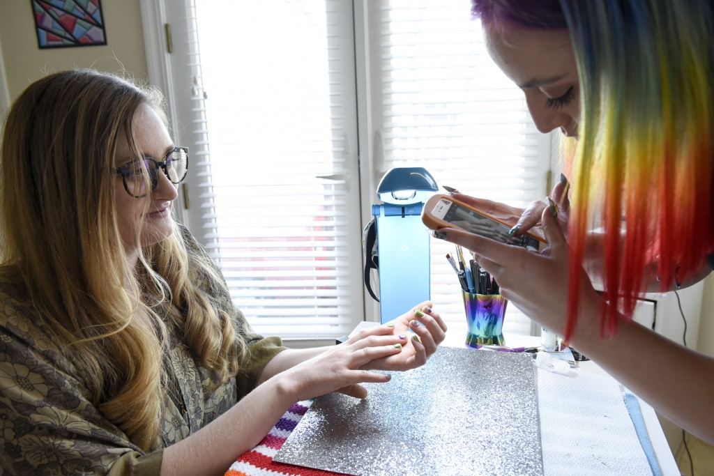 Christina Blea, right, takes pictures of the finished Cannabis themed manicure given to writer Emily Earlenbaugh, in Christina's Dabulous Nail Bar, at her home in Richmond, Calif., on Wednesday January 31, 2018.