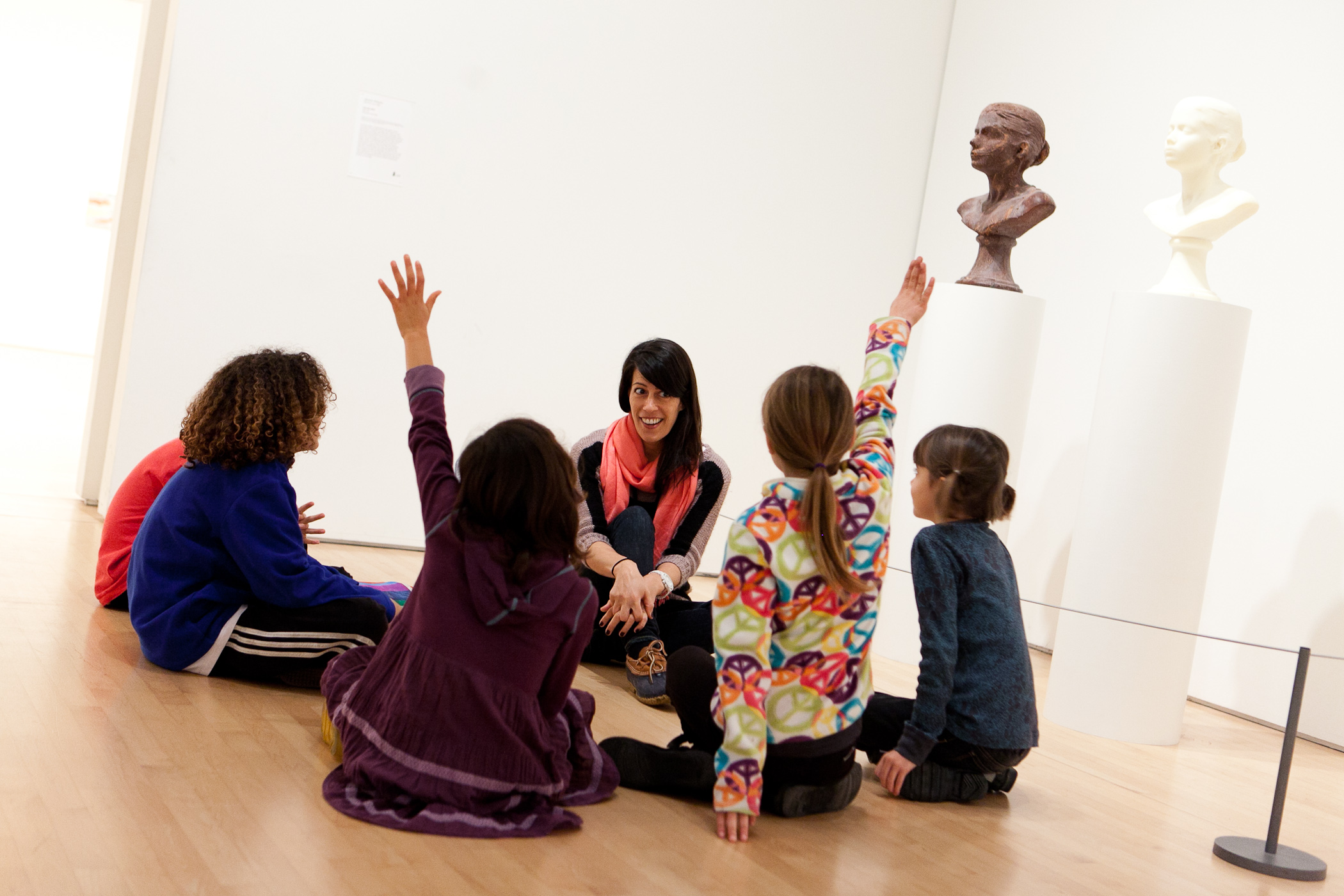 Children and a docent sitting on the floor of a gallery