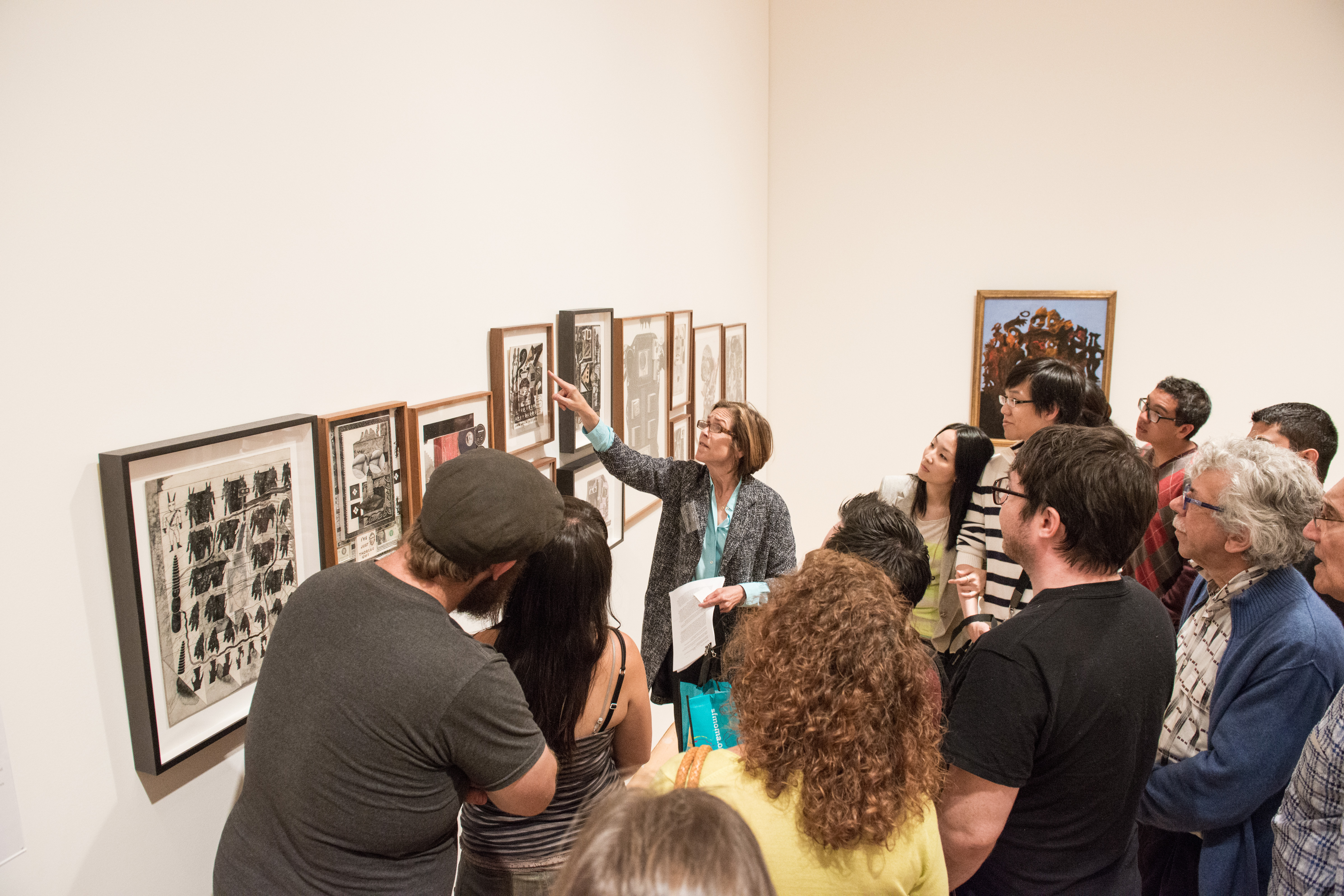A group of people looking closely at an artwork