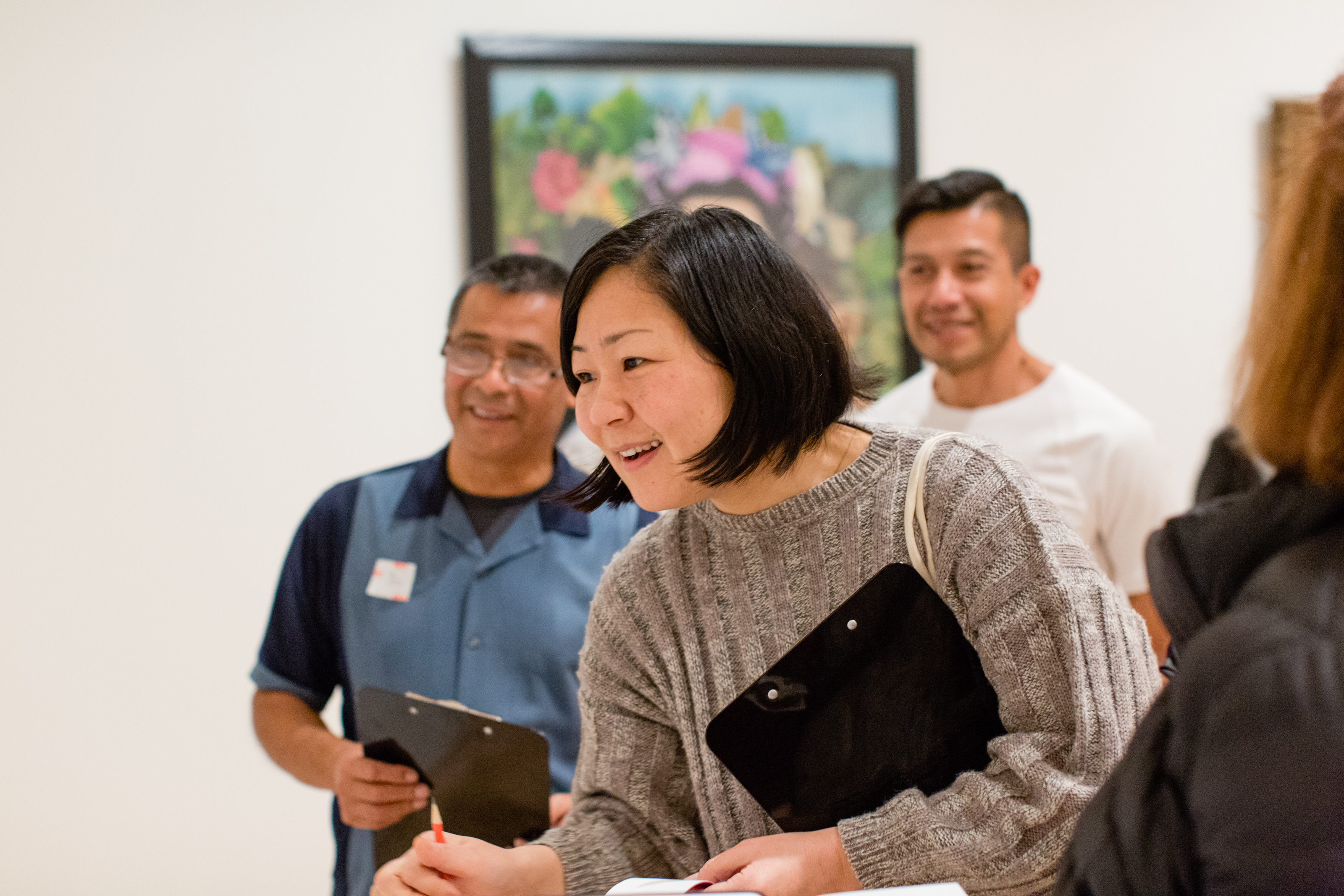 A smiling woman looks intently at something out of the frame in a gallery