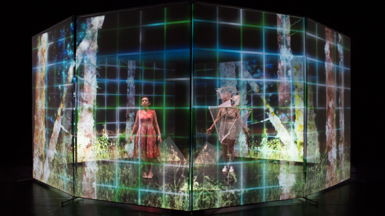 Two costumed performers stand behind an octagonal scrim with projected images