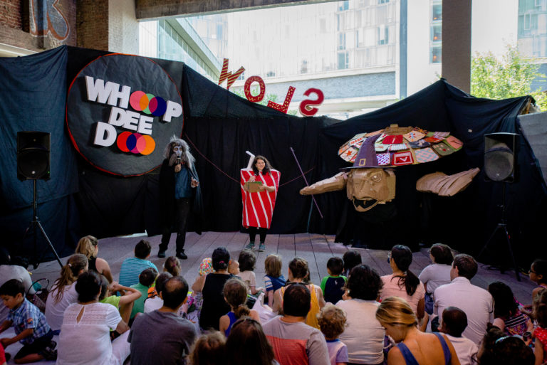 "Performers dressed as a werewolf and a soda can on a stage with a large witchy puppet and a sign reading, ""Whoop Dee Doo"" behind"