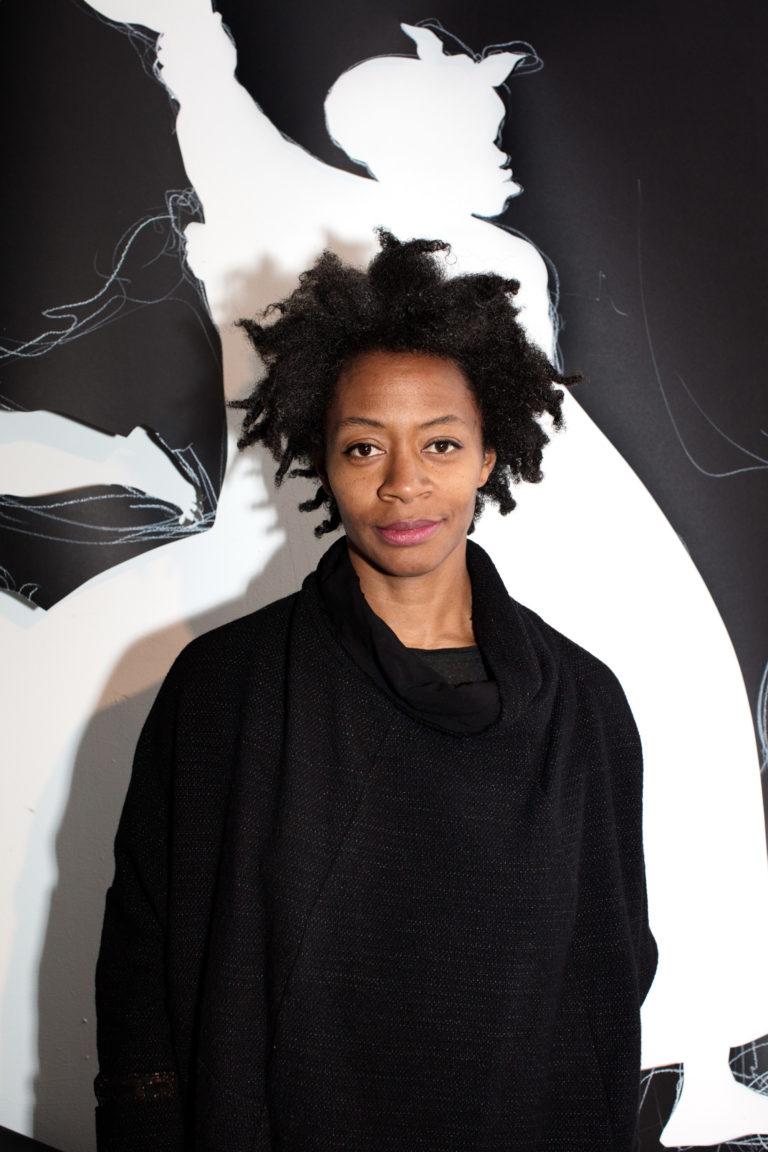 Portrait of artist Kara Walker in front of an artwork