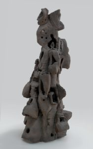 <p>This clay sculpture stands four and a half feet tall, is two and a half feet wide at its base, and is vaguely conical in shape. It resembles a gray desert hoodoo: a tall spire of rock, eroded into an irregular shape over time. The bottom portion of the sculpture features small caves and closed-in rooms with rough windows, giving the sculpture the appearance of a haphazard termite mound. Near the middle of the piece, the rooms and caves begin to stretch and distort, and resemble sagging, gaping mouths. Near the top, the caves and clay shapes become more abstract and decorative. Some of the stacked elements resemble crude masks or helmets, while others resemble melting bowls.</p>