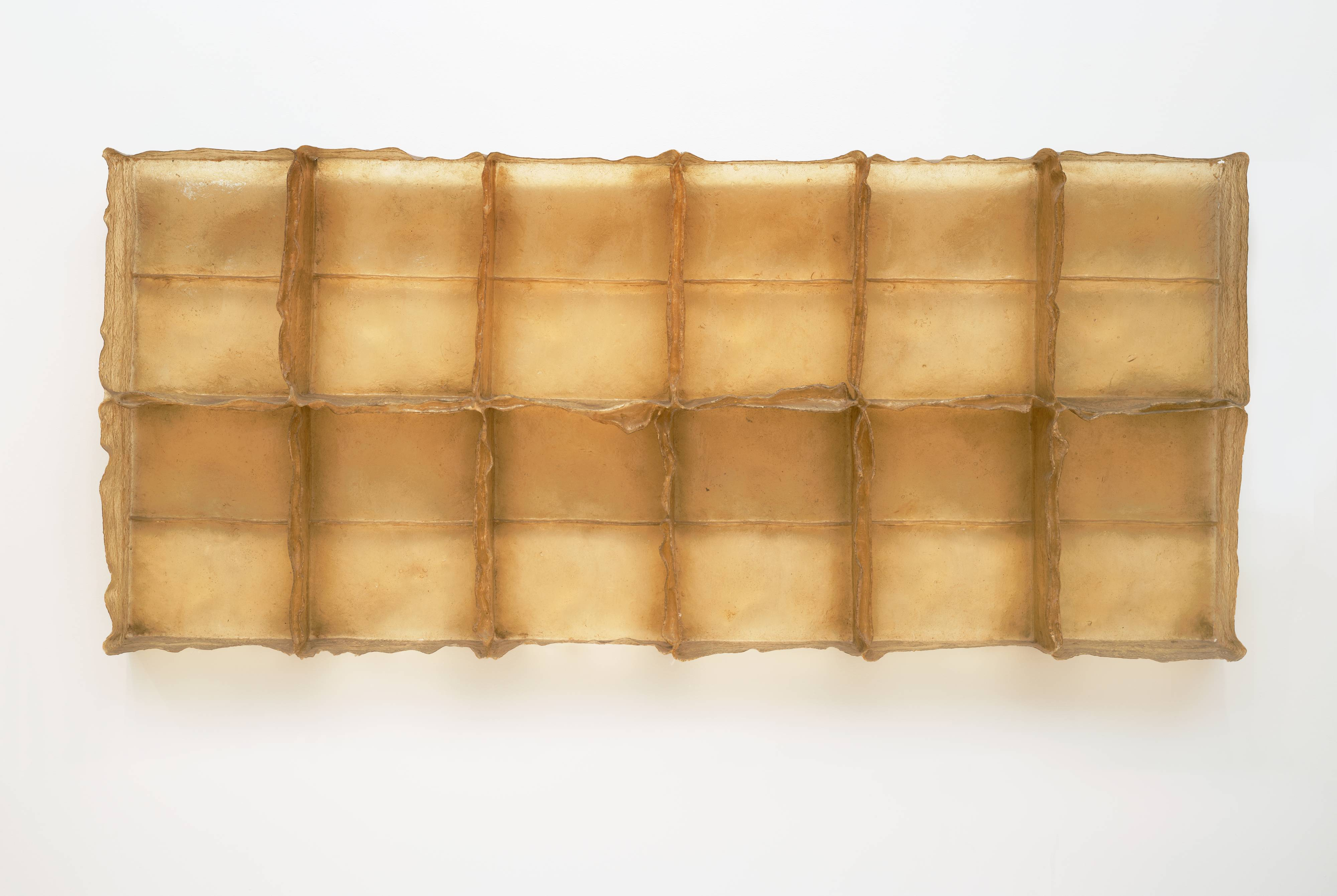 <p>This golden-yellow sculpture resembles a giant ice cube tray hanging horizontally on a wall, with the open, empty, rectangular niches facing us. The piece is more than three feet tall and over seven feet long with six niches on top and six on the bottom. Each individual compartment is divided in two by a thin horizontal line, giving the impression that there are, in fact, four rows of rectangles. The piece is constructed of fiberglass and polyester resin, giving it the look of golden honeycomb. The edges of the open boxes are imperfect and ragged, like peeling skin, in contrast to the structure itself, which is precise and orderly.</p>