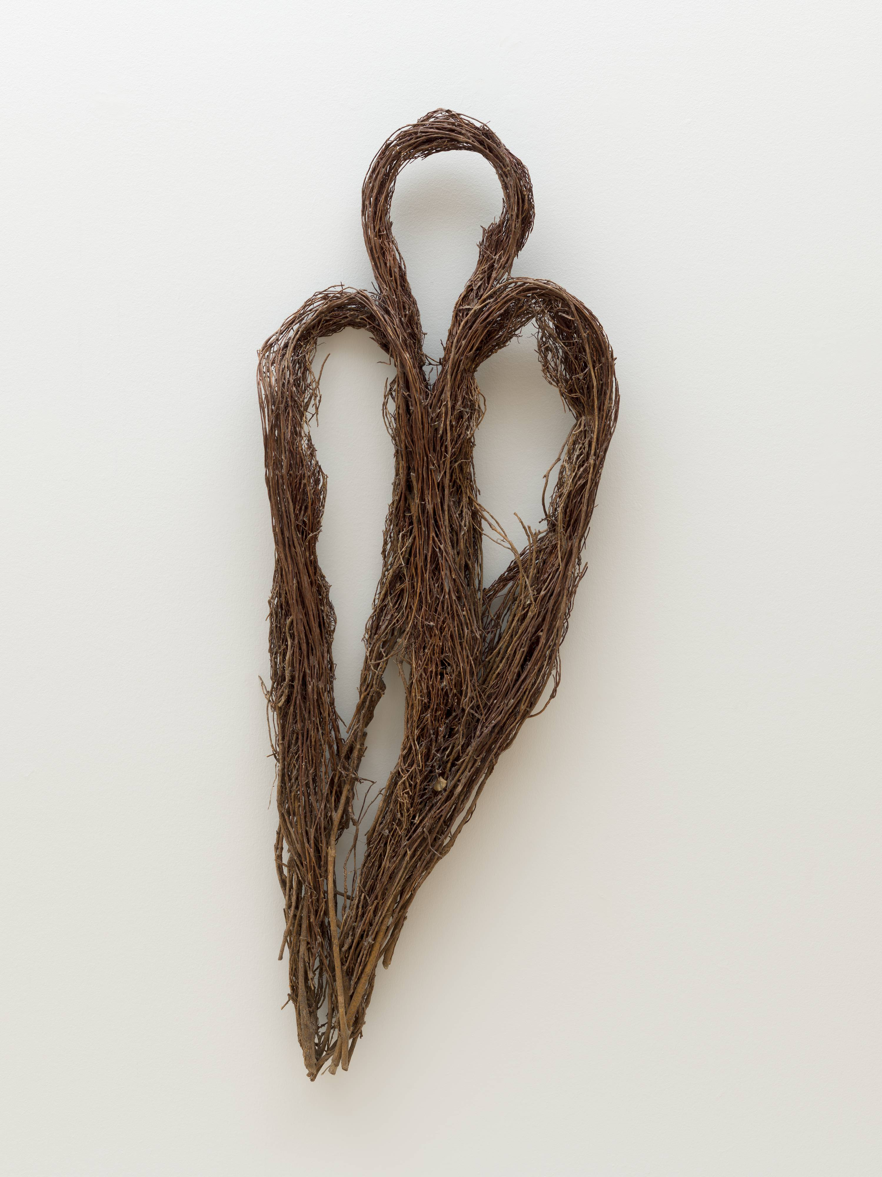 <p>This five foot tall [hanging?] sculpture comprises three loops of bent ficus-tree roots. The loops of bundled roots are long and thin, bent into smooth curves at the top and gathered to a point at the bottom. Individually they resemble the eyes of large sewing needles. Two of the loops have been positioned side-by-side to create an elongated heart shape. The third, slightly shorter loop has been slipped between them, adding an extra bump above the middle of the heart's arches. The thin brown roots are dry and wiry, and errant strands and small yellowed leaves poke out from the bundled loops in several places. No wires, strings, or binding agents are readily discernible.</p>