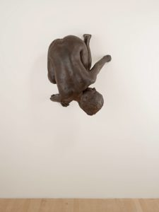 <p>This life-sized bronze sculpture depicts a small nude woman creeping down the wall like Spiderman, defying gravity. Curled up with her knees under her body, her rear end aimed at the ceiling, and her breasts pointing toward the wall, she glances back over her left shoulder with piercing glass eyes and a steely gaze. Her cast bronze body is dark brown in color and features rough textured patches, and raised seams that resemble thick veins. Her right hand and foot lie flat against the wall with clearly delineated fingers and toes, but on her left side her digits are missing, as if they've disappeared into the wall.</p>