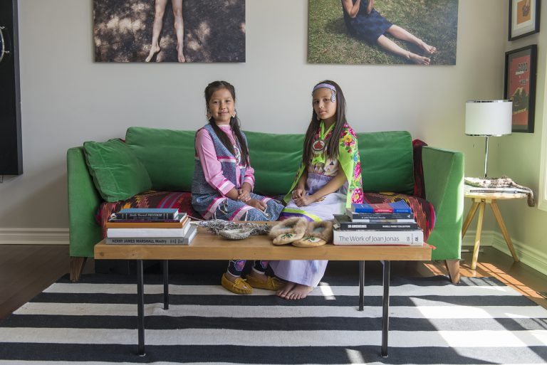 A photo of two girls sitting on a green sofa