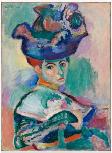 <p>Loose, sketchy brushstrokes and unnatural, vibrant colors are the defining features of this two foot wide, three-and-a-half foot tall oil portrait. The subject is a seated woman, depicted from the waist up, who sits in profile, but turns to face us with a stern expression. She wears an elaborate hat piled high with swatches of blue, burnt orange, and green, and holds an open fan in her gloved hand. Her face features patches of yellow, turquoise, and pink, and her nose and forehead are marked with thick green lines. While the woman has been rendered, in part, with thick smears of paint and heavy brushstrokes, the background is composed of muted blotches of pastel greens, violets, pinks, and yellows that appear to have been created with a nearly dry paintbrush.</p>