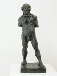 <p>This three foot tall cast bronze statue depicts a stocky nude man with arms truncated above the elbow. The man stands on a square bronze plinth with his feet shoulder-width apart, and his left foot ahead of the right. His head is slightly oversized, with wavy hair, a strong brow, and a full beard. Chin to chest, he stares in the direction of his forward foot with a neutral expression. He has thick, chunky muscles in his legs, chest, neck and shoulders, and his scrotum hangs heavy and low. The charcoal-colored cast bronze appears modeled by hand like soft clay, with deep finger marks covering the surface.</p>