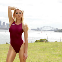 Mel in a maroon and purple high leg, racerback Asics swimsuit