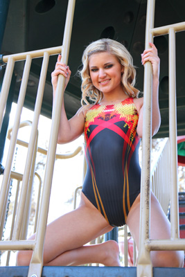 Cyierra in a yellow, red, orange and black racerback Tornado swimsuit
