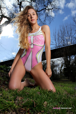 Ashley Light in a baby pink, gold, white and hot pink racerback JKUSS swimsuit
