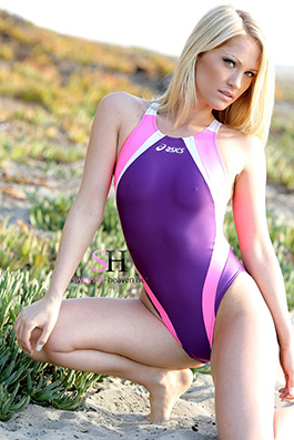 Shannyn in a baby pink, purple and white high leg, racerback Asics swimsuit