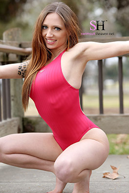 Kitt Katt in a hot pink high leg Speedo swimsuit