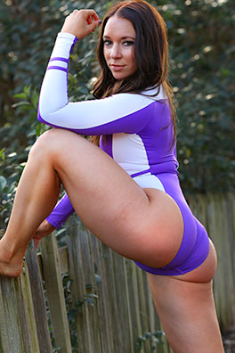 Flex in a purple and white high leg, high neck, long sleeve, zipper back Realise swimsuit