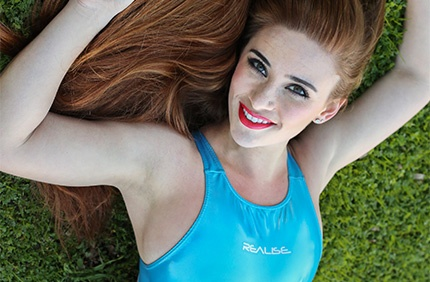 Ginger in a blue and baby blue rubberised, racerback Realise swimsuit