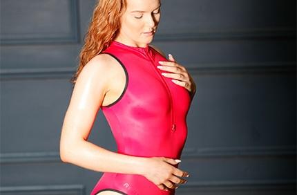 Kandice in a hot pink zipper front, high neck, high leg Realise swimsuit