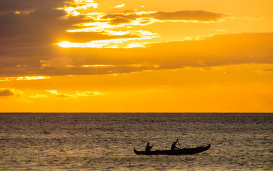 Silhouette of two men paddling a Hawaiian outrigger canoe at sunset, Maui, Hawaii, USA