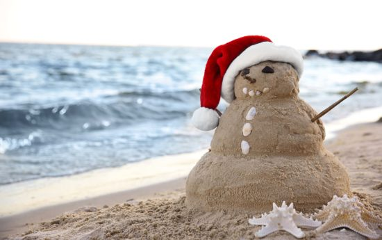 Snowman made of sand on beach. Christmas holiday concept