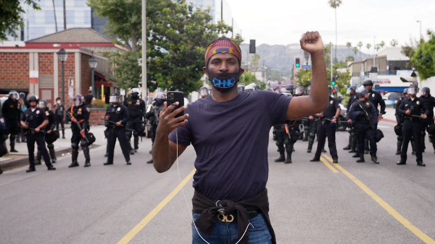 Video screenshot of man, staring into the camera with a fist raised, as he stands in front of a line of police officers.