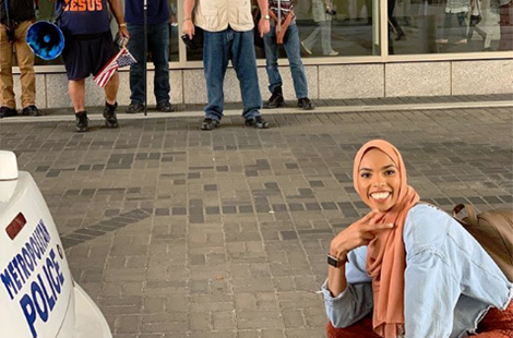 Muslim woman poses in front of anti-Islam protesters