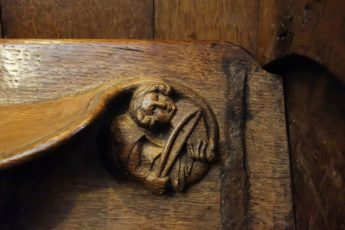 A musician bows a stringed instrument in this wood carving in Winchester Cathedral in the south of England.