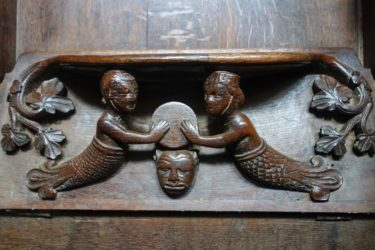 This 13th century misericord in Exeter Cathedral depicts a mermaid and a merman holding a drum or cymbal.