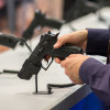 hands holding a gun at display desk