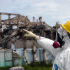 man in hazmat suit pointing to damaged Fukushima reactor