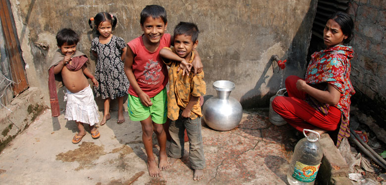 Woman and children at water standpipe in Dhaka