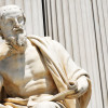 Statue of ancient philosopher holding a scroll. / Photo: Shutterstock