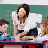 teacher assisting elementary grade students / racorn/Shutterstock