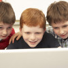 Three school-age boys looking at a laptop computer/Monkey Business Images, Shutterstock