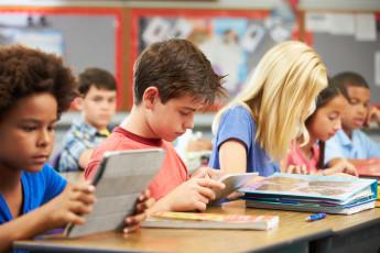 elementary school students reading at classroom desks