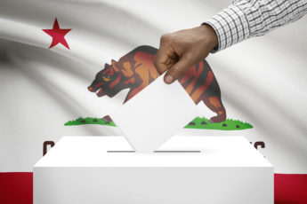 hand putting a ballot in ballot box with California flag in background