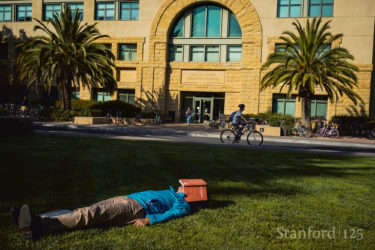 Student lying on grass.