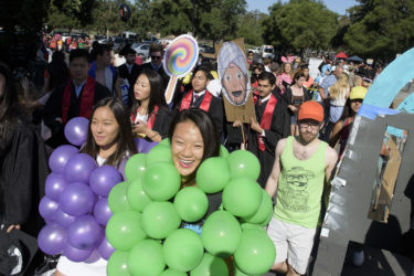 Students wearing balloons crowd near the gate to Stanford Stadium before Wacky Walk