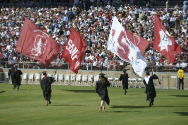 The Axe Committee flag bearers sprint onto the field