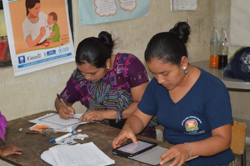 Health promoters with a tablet computer using app to track children's nutrtion